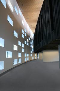 Saint-Malo. Médiathèque. Architecte : Architecture studio. Certains percements laissent passer la lumière naturelle, d'autres, occultés, sont équipés d'éclairage artificiel. La mixité de ces apports de lumière crée une palette de blancs.