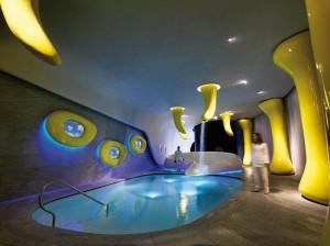 Dans le centre de bien-être,  des formes fluides définies en jaune  sortent de terre à différentes hauteurs,  d'autres, tachetées d'encastrés Pixel  Plus LED, descendent du plafond, le  perçant et emmenant avec elles des  cascades d'eau